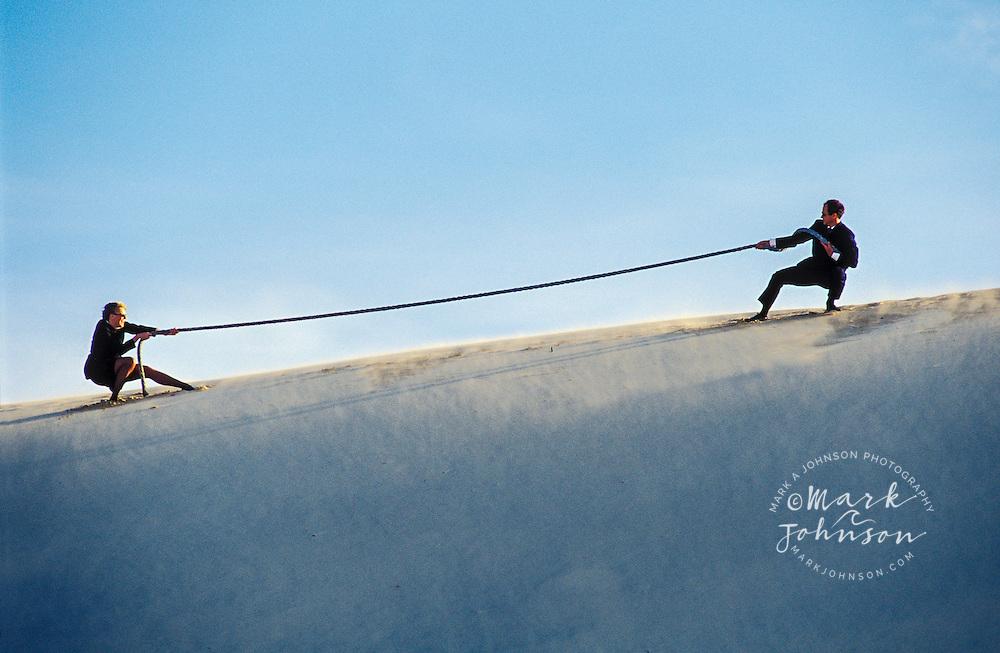 Businessman & businesswoman couple having a tug-o-war on sand dune