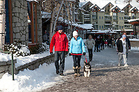 A couple enjoys strolling and shopping Whistler village on a winter day.