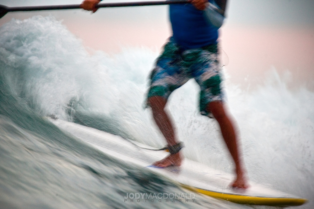 John Amundson glides across a wave at sunset in Sumba Indonesia.  I wanted to capture his amazing footwork and this shot blurred everything, giving it a great sense of motion.