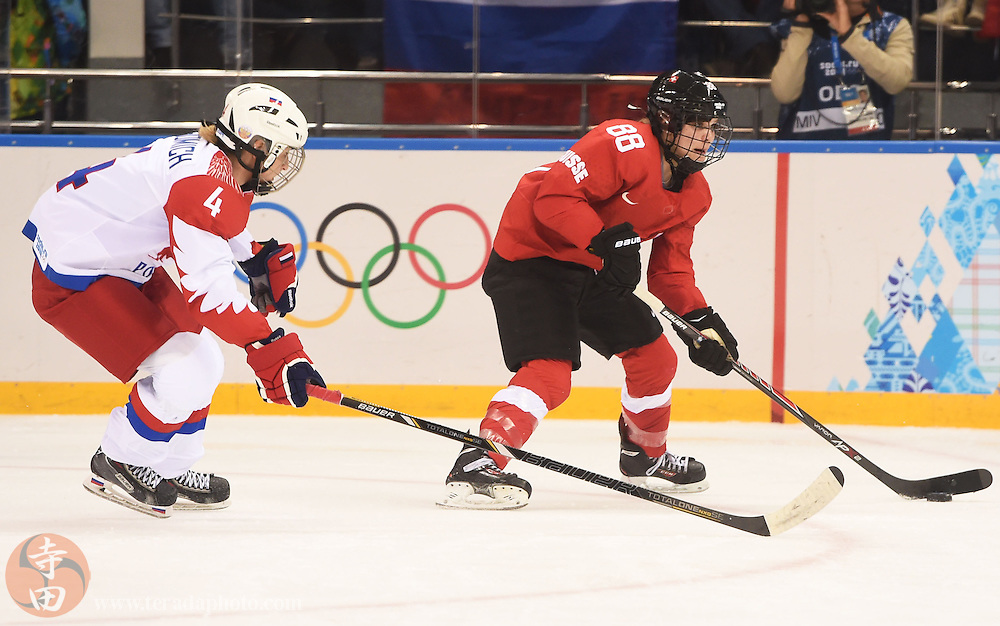 Feb 15, 2014; Sochi, RUSSIA; Russia forward Yekaterina Smolina (88) skates with the puck as Russia defenseman Alyona Khomich (4) defends in a women's quarterfinals ice hockey game during the Sochi 2014 Olympic Winter Games at Shayba Arena.