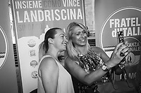 COMO, ITALY - 21 JUNE 2017: Giorgia Meloni (left), leader of the Fratelli d'Italia party, takes a selfie with a supporter at the end of Mr Landriscina's rally in Como, Italy, on June 21st 2017.<br /> <br /> Residents of Como are worried that funds redirected to migrants deprived the town's handicapped of services and complained that any protest prompted accusations of racism.<br /> <br /> Throughout Italy, run-off mayoral elections on Sunday will be considered bellwethers for upcoming national elections and immigration has again emerged as a burning issue.<br /> <br /> Italy has registered more than 70,000 migrants this year, 27 percent more than it did by this time in 2016, when a record 181,000 migrants arrived. Waves of migrants continue to make the perilous, and often fatal, crossing to southern Italy from Africa, South Asia and the Middle East, seeing Italy as the gateway to Europe.<br /> <br /> While migrants spoke of their appreciation of Italy's humanitarian efforts to save them from the Mediterranean Sea, they also expressed exhaustion with the country's intricate web of permits and papers and European rules that required them to stay in the country that first documented them.