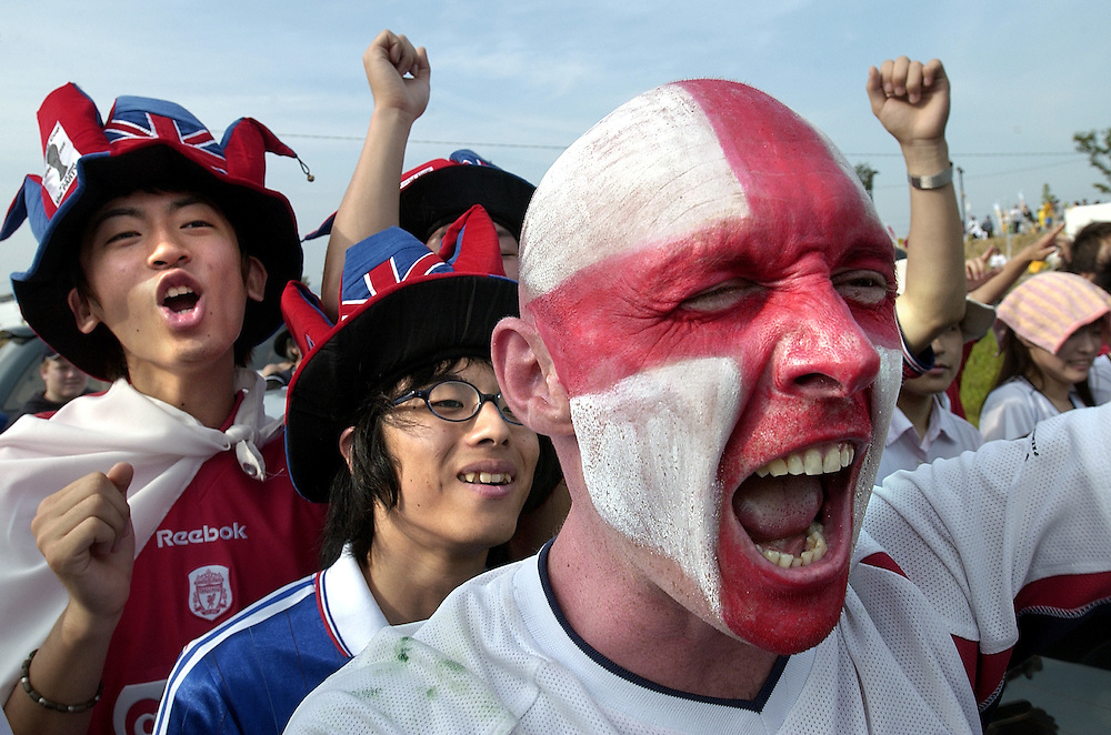 Japanese join in with English supporters outside Shizuoka Stadium to support England in its match against Brazil in the World Cup. Shizuoka Japan 21/06/02..©David Dare Parker/AsiaWorks Photography