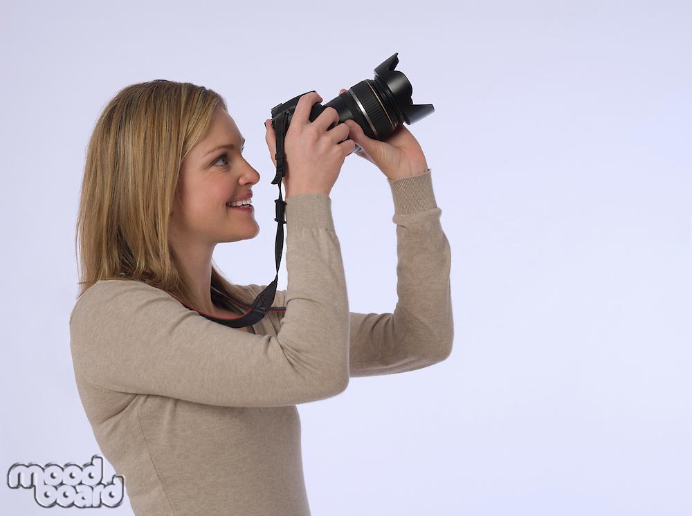 Young (20-25 years) female photographer holding camera studio shot