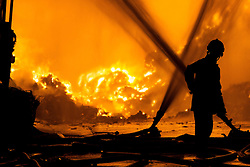 © Licensed to London News Pictures . 21/08/2013 . Stockport , UK . A firefighter is silhouetted against the intense blaze at the J25 Recycling Centre in Bredbury , Stockport this morning (Wednesday 21st August 2013) where a building and bales of recyclable material are alight . The fire , which started late last night (20th August) is being tackled by more than 50 fire crew . The site , which is adjacent to a branch of Morrisons Supermarket and McDonalds , is off Junction 25 of the M60 motorway , exits for which are closed in both directions . Photo credit : Joel Goodman/LNP