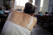 young adult woman in a church seen from behind