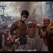 "In this ""Signature Series"" image by David Longstreath devotees at the Vegetarian Festival in Phuket, Thailand are seen as fireworks expolde around them during a street procession.  The annual festival in Phuket is held on a annual basis and begins usually in late September of early October depending on the lunar cycle."