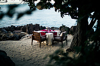 A private dining table beneath coconut trees near the beach at Four Seasons in Koh Samui, Thailand.