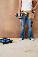 Woman with toolbelt and drill leaning against wall low section