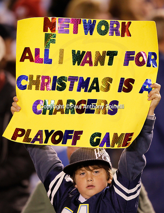 A San Diego Chargers fan holds a sign wishing for a playoff game as a Christmas present during the NFL week 15 football game against the San Francisco 49ers on Thursday, December 16, 2010 in San Diego, California. The Chargers won the game 34-7. (©Paul Anthony Spinelli)