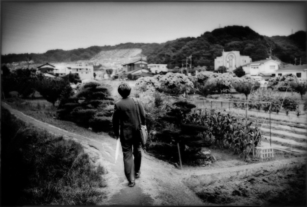 Young Japanese salariman walks home through last few farms from the commuter train station on his way home after work in a western Tokyo suburb, Naganuma, Tokyo, Japan.