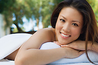 Young woman lying on massage table, outdoors, portrait