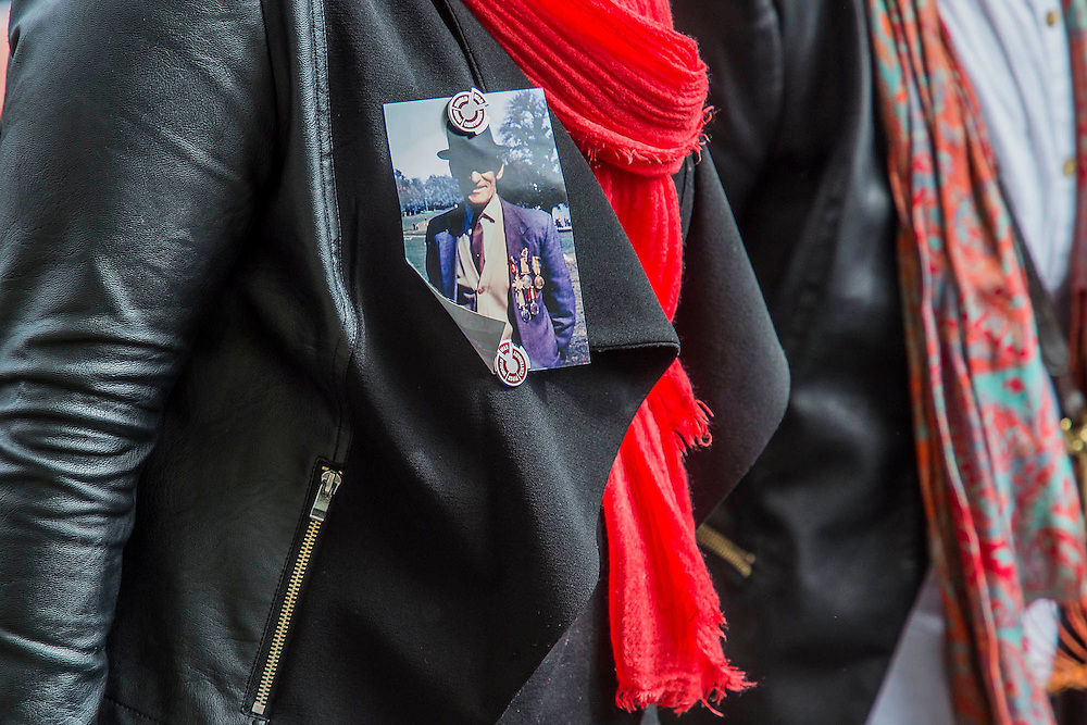 A woman wears a picture of a relative as veterans and descendants march past. A commemoration in London to mark the Centenary of the Gallipoli Campaign 25 April 2015 at the Cenotaph on Whitehall, Westminster. Descendants of those who fought in the campaign also march past, led by military personnel, as part of the ceremony. This is an addition to the usual annual ceremony organized byvThe High Commissions of Australia and New Zealand.Guy Bell, 07771 786236, guy@gbphotos.com