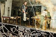 Woluwe-Saint-Lambert. 20 februari 2013 Jongeren bezig met houtsnedes in jongerencentrum Antichambre asbl - Zij zullen na het drukken van de houtsnedes op grote vellen papier, in het mim, muziekinstrumentenmuseum , een performance ondersteunen tijdens de museum nightfever.Een zwart geinkte houtgravure, met de workshop in de spiegel gereflecteerd.