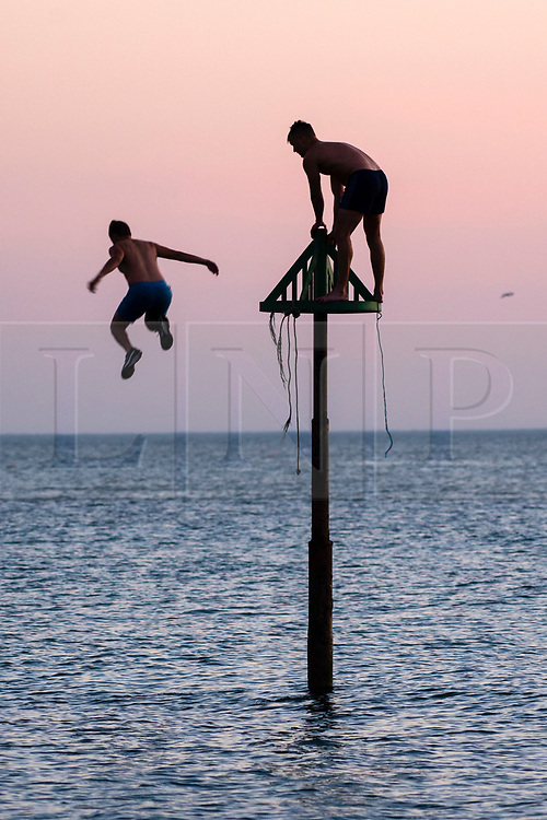 © Licensed to London News Pictures. 02/07/2018. Aberystwyth, UK. Young men jumping into the cool sea in Aberystwyth at the end of yet another scorchingly hot and cloudless day, as the prolonged heatwave continues to dominate the weather over the UK. Photo credit: Keith Morris/LNP