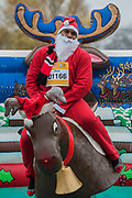 Riding the bucking reindeer - Participants of all ages don Santa suits for the London Santa Dash on Clapham Common. The event was to raise money for the Great Ormond Street Hospital (GOSH) Children's Charity and involved a 5 or 10k run.