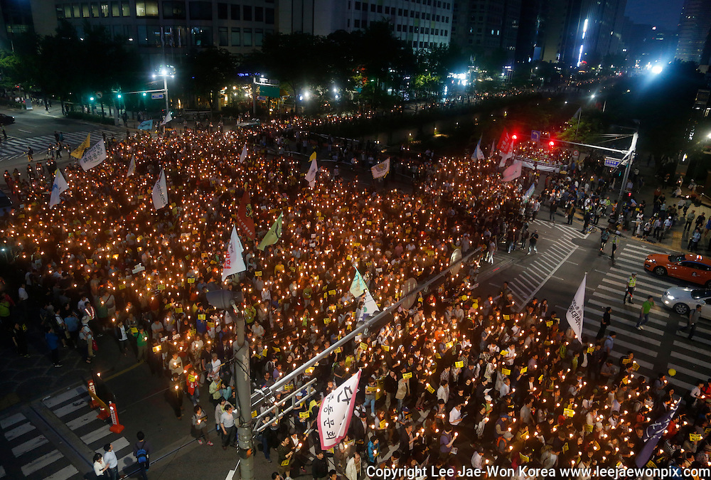 Participants march during a candle-lit protest against South Korean government in Seoul May 24, 2014. According to local media, about 30,000 South Koreans demonstrated on Saturday to mourn for the victims of Sewol ferry and to wish for the return of missing passengers as they demanded to investigate President Park Geun-Hye and reveal the facts of the ferry tragedy which left more than 300 people dead or missing after it was sunken in southwestern waters of the country on April 16, 2014. (Photo by Lee Jae-Won/SOUTH KOREA)