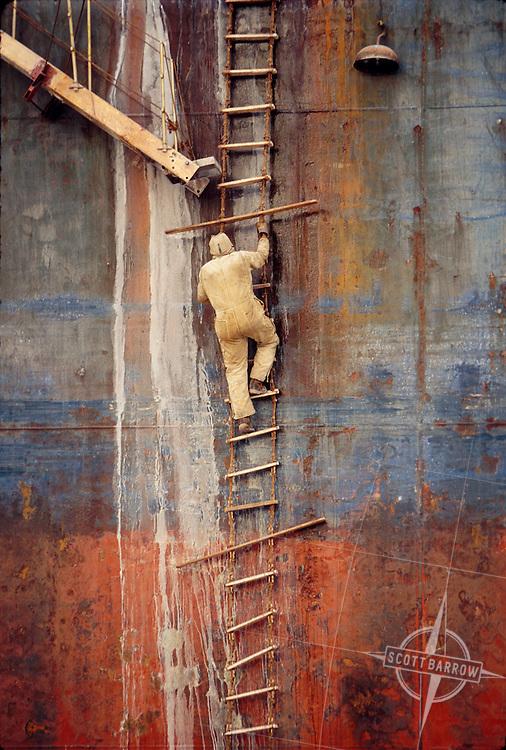 Shipyard worker climbing rope ladder on cargo ship under repair.