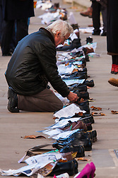 London, December 10th 2014. The shoes of hundreds of victims who died in Ireland, North and South during the Troubles are lined up opposite Downing Street as families demand that a proper investigation into over 3,600 deaths and 40,000 injuries on all sides, sets the truth free. PICTURED: A man reads the stories and messages tied to each pair of shoes by relatives of those long dead, who want the truth set free.