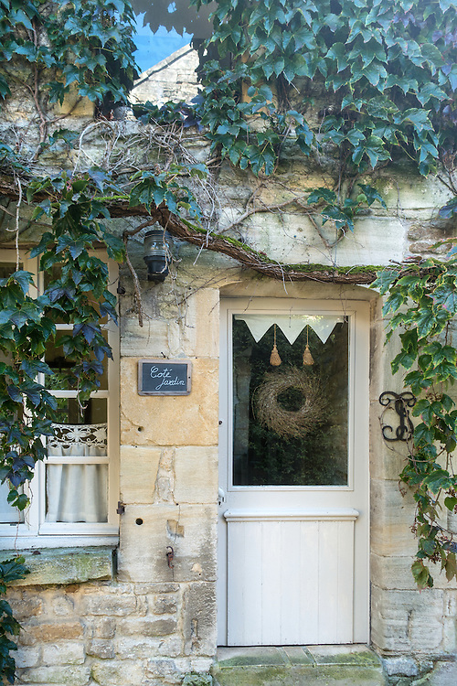 Moss covered green leafy vines cling to the wall of a beige stone house in rural France. A door and part of a window with white lace curtains are visible below the vines.