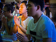 "04 MARCH 2015 - BANGKOK, THAILAND:  People pray in the ""wiharn"" or prayer hall at Wat Benchamabophit on Makha Bucha Day. Makha Bucha Day is an important Buddhist holy day and public holiday in Thailand, Cambodia, Laos, and Myanmar. Many people go to temples to perform merit-making activities on Makha Bucha Day. Wat Benchamabophit is one of the most popular Buddhist temples in Bangkok.   PHOTO BY JACK KURTZ"