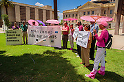 "31 JULY 2012 - PHOENIX, AZ:  Members of Code Pink stand in front of the Arizona State Capitol in Phoenix during a press conference with Medea Benjamin, the founder of Code Pink, Tuesday. Benjamin is a political activist, best known for co-founding Code Pink and, along with her husband, activist and author Kevin Danaher, the fair trade advocacy group Global Exchange. She was also a Green Party candidate in 2000 for the United States Senate. She appeared in Phoenix to promote her new book, ""Drone Warfare: Killing by Remote Control."" She, and other members of Code Pink, presented a letter to Arizona Gov. Jan Brewer protesting Brewer's request to use the state's airspace to train drone pilots.  PHOTO BY JACK KURTZ"