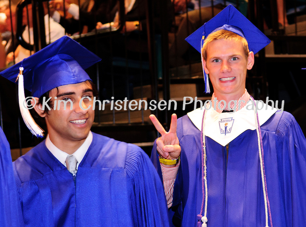 Andrew Saghafi looks on as Chandler Segar flashes the peace sign while walking into the Friendswood High School Graduation held at Moody Gardens.