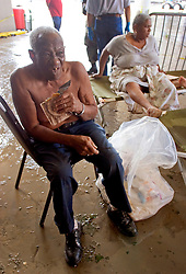 30 August, 2005. New Orleans Louisiana. Hurricane Katrina aftermath. <br /> Rescued from the flooded lower 9th ward by the Louisiana National Guard, an elderly man is given an MRE at the makeshift hospital triage unit set up at the Superdome in New Orleans.<br /> Photo Credit: Charlie Varley/varleypix.com