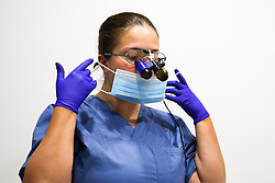 © Licensed to London News Pictures. 13/02/2020. London, UK. A dentist putting a surgical face mask for a patient examination at a dental surgery in north London. <br /> UK dentists issue warning that they are running out of face masks due to the coronavirus outbreak. The British Dental Association (BDA) has warned that surgeries are at risk of running out of surgical face masks by the middle of next week and will not be able to treat patients safely under current rules. Photo credit: Dinendra Haria/LNP<br /> <br /> ***Permission Grant***