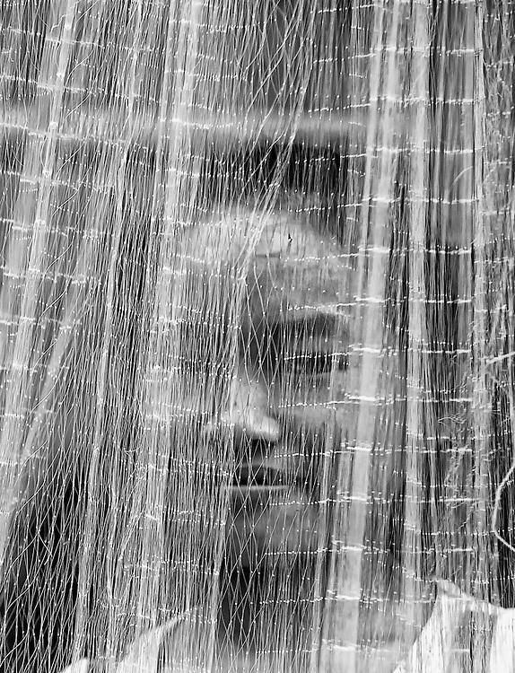 A Khamu girl behind a fishing net near Nong Kiau, Laos.
