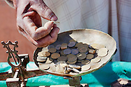 Hand of a market vendor holding Moroccan Dirham coins as change at the market in Tagounite, Morocco.