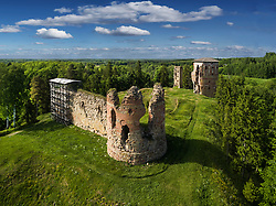 Ruins of Vastseliina Bishop castle in Estonia. Aerial, green grass and forest, clouds