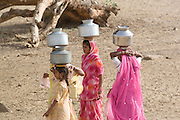 India, Rajasthan, Masuria, women and girls carrying water from the well back to the village