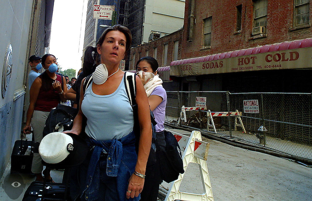 Residents from buildings just two blocks from the World Trade Center were allowed by police to return home for the first time on 9/16/01. They removed belongings moving up Albany street and out of the controlled area.