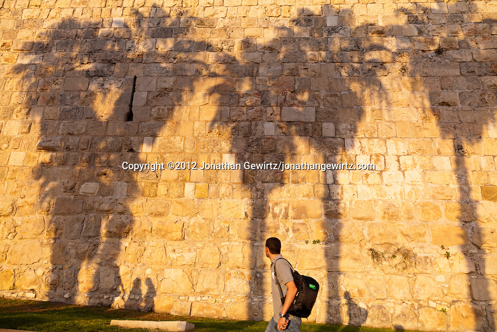 People and palm trees cast shadows on a section of the stone exterior wall of the Old City of Jerusalem. WATERMARKS WILL NOT APPEAR ON PRINTS OR LICENSED IMAGES.