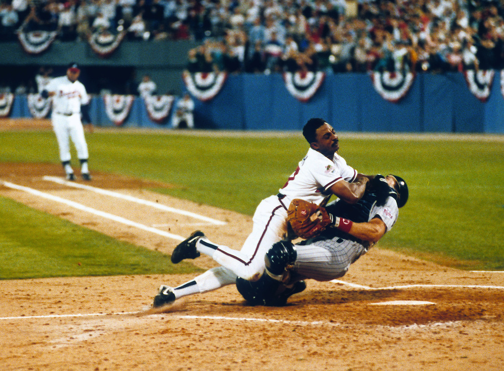 ATLANTA, GA-OCTOBER 23:  Lonnie Smith of the Atlanta Braves bowls over Brian Harper of the Minnesota Twins during Game 4 of the 1991 World Series at Fulton County Stadium in Atlanta, Georgia on October 23, 1991.  Smith was out on the play.  The Twins won the series  4-3. (Photo by Ron Vesely)