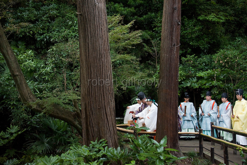"""A priest and maiko attendants release bell crickets that have been dedicated to the shrine """"kami"""" (gods) during the suzumushi-hojosai rite that marks the end of the  3-day Reitaisai festival in Kamakura, Japan on  14 Sept. 2012.  The ritual is observed in order to recognize the preciousness of life, releasing the insects by a pond inside the shrine grounds. Photographer: Robert Gilhooly"""