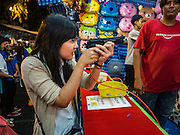 20 NOVEMBER 2015 - BANGKOK, THAILAND: An high school student uses a bb gun pistol at an arcade shooting game at the Wat Saket temple fair. Wat Saket is on a man-made hill in the historic section of Bangkok. The temple has golden spire that is 260 feet high which was the highest point in Bangkok for more than 100 years. The temple construction began in the 1800s in the reign of King Rama III and was completed in the reign of King Rama IV. The annual temple fair is held on the 12th lunar month, for nine days around the November full moon. During the fair a red cloth (reminiscent of a monk's robe) is placed around the Golden Mount while the temple grounds hosts Thai traditional theatre, food stalls and traditional shows.     PHOTO BY JACK KURTZ