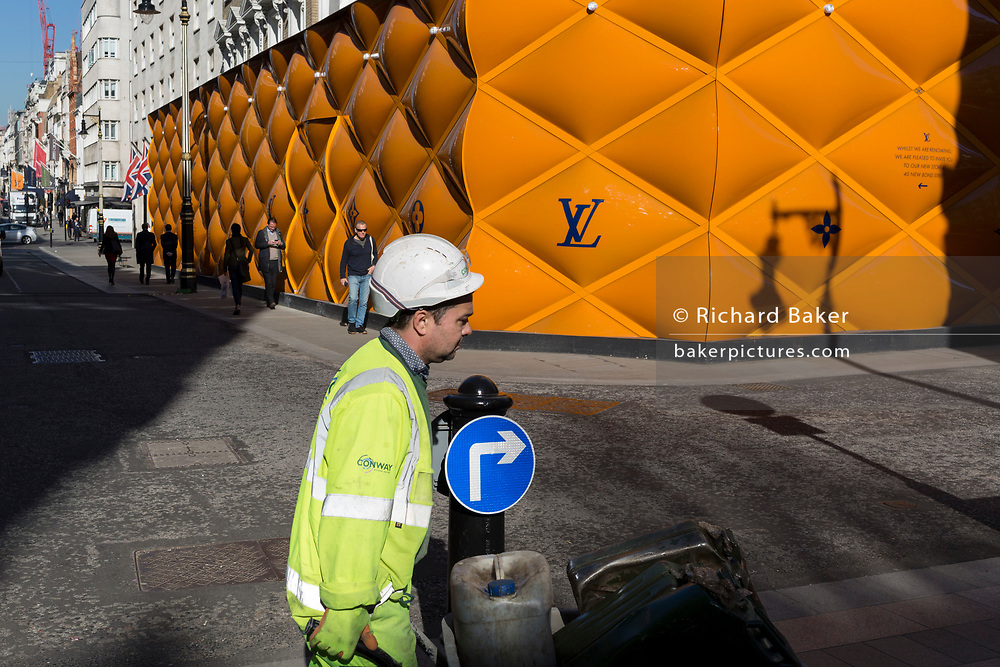 A construction workman pushes a wheelbarrow past the temporary renovation hoarding of luxury brand Louis Vuitton in New Bond Street, on 25th February 2019, in London, England.