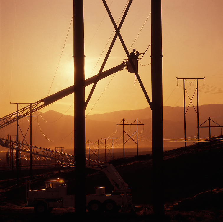 electrical workers repairing high voltage lines at sunset in the Nevada desert outside of Las Vegas