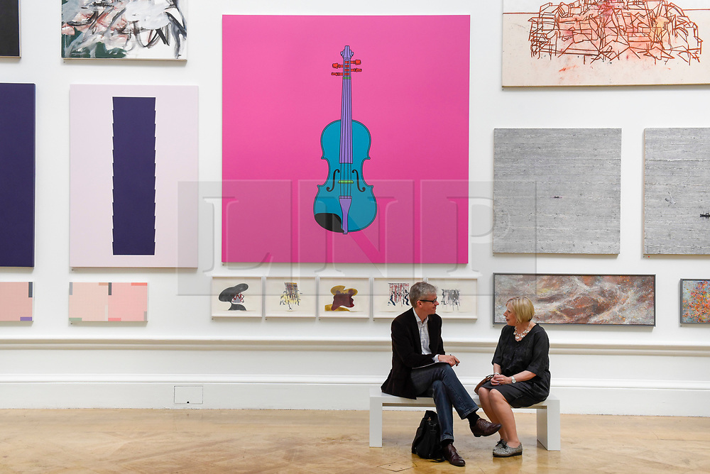 """© Licensed to London News Pictures. 08/06/2017. London, UK. Visitors sit in front of (C) """"Untitled (Violin)"""" by Sir Michael Craig-Martin RA (GBP120,000).  Preview of the Summer Exhibition 2017 at the Royal Academy of Arts in Piccadilly.  Co-ordinated by Royal Academician Eileen Cooper, the 249th Summer Exhibition is the world's largest open submission exhibition with around 1,100 works on display by high profile and up and coming artists.<br />  Photo credit : Stephen Chung/LNP"""