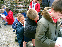 Children from a North Yorkshire primary school on a field trip; writing notes on each others backs; UK