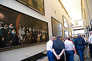 tourists walking through a gallery with old portrait paintings Amsterdam Historical Museum