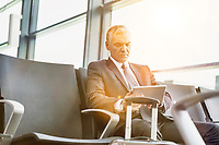 Mature businessman using digital tablet while sitting and waiting for boarding in his gate at airport
