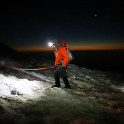 A climber uses a headlamp during the beginning of dawn near the top of Disappointmentment Cleaver as teams ascend Mount Rainier on June 30, 2015. The iconic Pacific Northwest volcano is a popular challenge for mountaineers.  (Joshua Trujillo, seattlepi.com)
