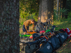 Bike packing in the High Black Forest. Mountain biker (M49) taking a rest, in the background Mountain bike with Bike packing-equipment, Baden-Wuerttemberg, Germany