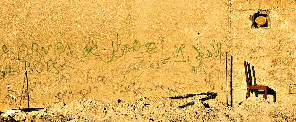 An abandoned chair lies by a grafitti filled wall in Satwa, Dubai on Jan 28, 2005 Archive of images of Dubai by Dubai photographer Siddharth Siva