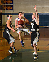 Gilford's Max Troiano jumps in between Prospect Mountain's Nate Farnham and Logan LaRoche during championship action in the Holiday Basketball Tournament Monday night at GHS.  (Karen Bobotas/for the Laconia Daily Sun)
