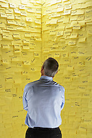 Middle-aged man standing in front of wall covered in sticky notes back view