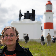 A REQUIEM FOR THE FOGHORN, PERFORMED BY SEVENTY FIVE BRASS PLAYERS, A FOGHORN AND AN ARMADA OF SHIPS<br /> A project by Danish artist, Lise Autogena, in collaboration with Joshua Portway and composer Orlando Gough. Ships horns from an armada of vessels off-shore, seventy five brass players on-shore and the Souter Lighthouse Foghorn  performed a Foghorn Requiem, an ambitious musical performance to mark the disappearance of the sound of the foghorn from the UK's coastal landscape.<br /> Conducted and controlled from a distance, ships at sea sounded their horns to a musical score, that will took into account landscape and the physical distance of sound. The performance took place by Souter Light House by South Shields, UK with 8-10.000 spectators and more than 50 ships off-shore.<br /> Lise Autogena by the fog horn and light house.
