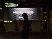 15 OCTOBER 2016 - BANGKOK, THAILAND:  A woman walks past the official announcement of the death of Bhumibol Adulyadej, the King of Thailand, in the Asoke BTS Skytrain station in Bangkok. A photo of King Bhumibol is above the announcement. King Bhumibol Adulyadej died Oct. 13, 2016. He was 88. His death comes after a period of failing health. With the king's death, the world's longest-reigning monarch is Queen Elizabeth II, who ascended to the British throne in 1952. Bhumibol Adulyadej, was born in Cambridge, MA, on 5 December 1927. He was the ninth monarch of Thailand from the Chakri Dynasty and is known as Rama IX. He became King on June 9, 1946 and served as King of Thailand for 70 years, 126 days. He was, at the time of his death, the world's longest-serving head of state and the longest-reigning monarch in Thai history.     PHOTO BY JACK KURTZ